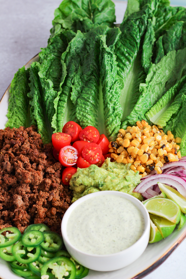 Platter with lettuce, roasted corn, tomatoes and ground beef with bowl of ranch dressing