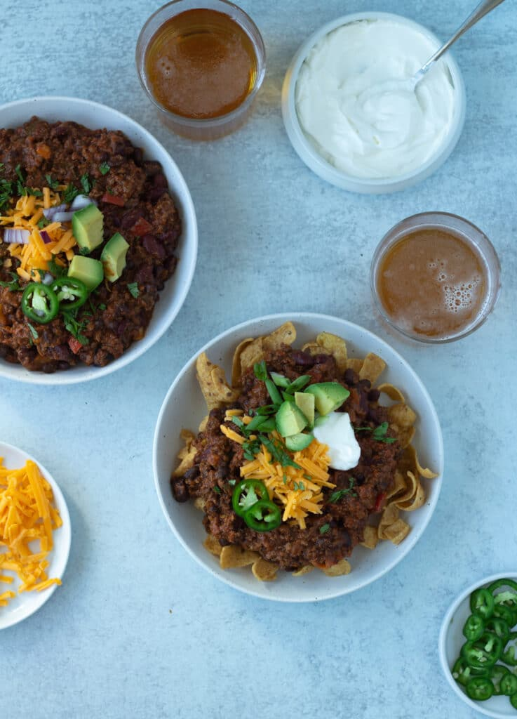 two bowls of chili with beer on side