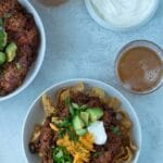two bowls of chili with toppings and glass of beer