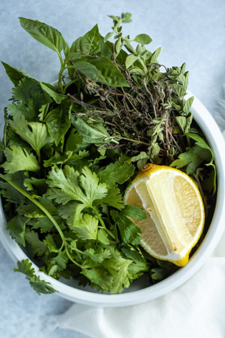 Bowl of herbs including basil, oregano and lemon