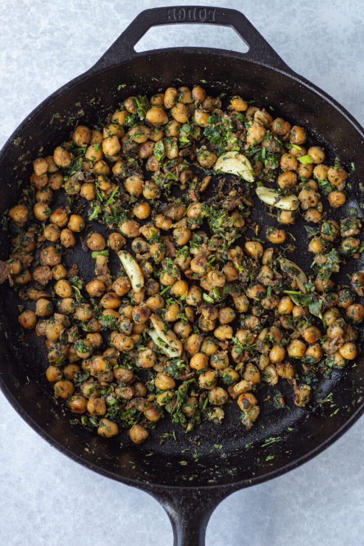 Cast iron pan with crispy chickpeas mixed with garlic and herbs