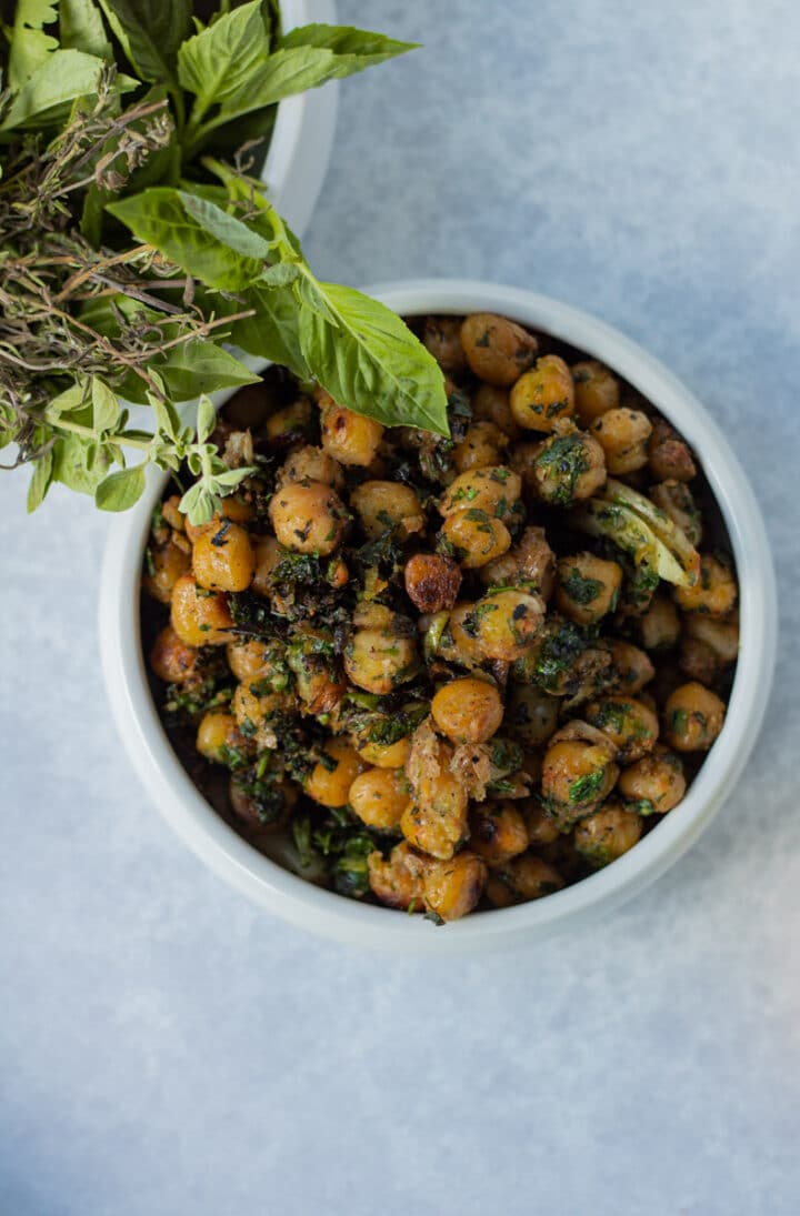 small bowl of pan fried chickpeas with glass of herbs