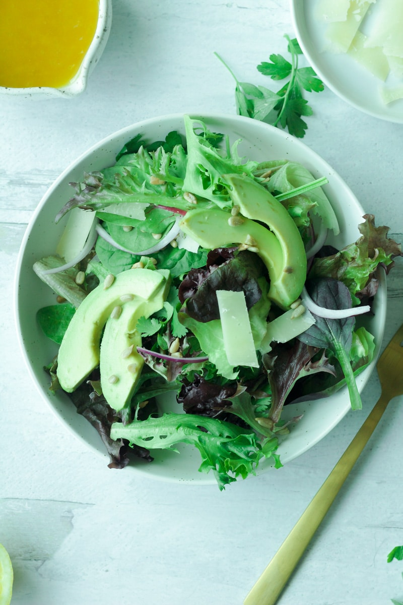 Plate of mixed salad with greens, avocado, sunflower seeds, red onion slices and dressing with fork