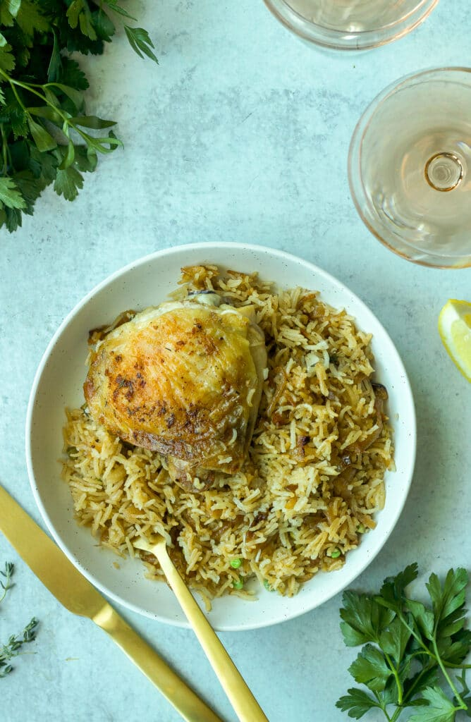 plate with chicken and rice and gold silverware with parsley leaves and lemon wedges around plate