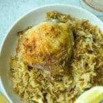 closeup shot of garlic chicken and rice on plate with lemon wedge