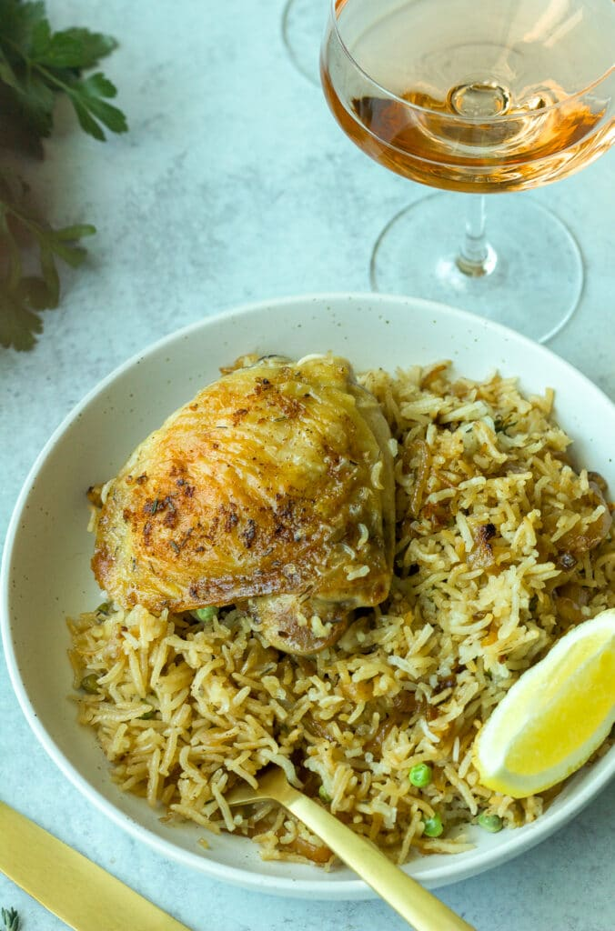 Plate of garlic rosé chicken and rice with lemon wedge and glass of wine