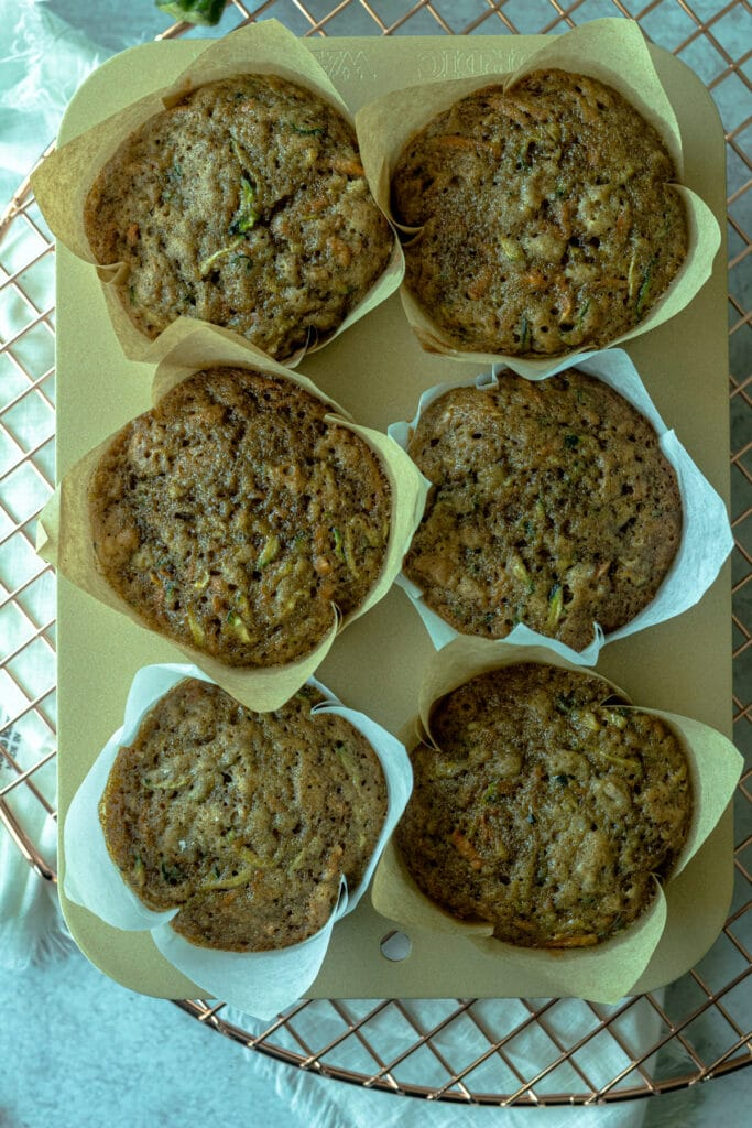 baked muffins in pan on wire rack