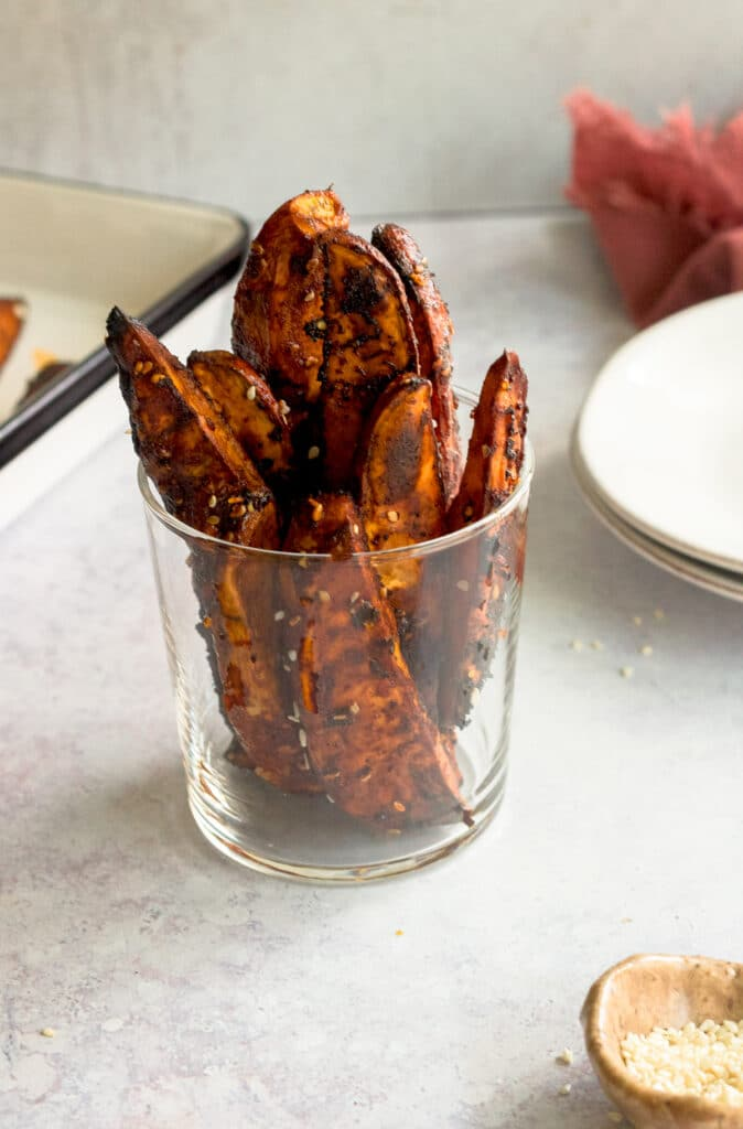 gochujang sweet potatoes in glass with small bowl of sesame seeds